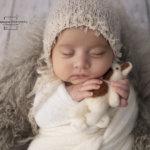 little newborn girl holding a teddy bear